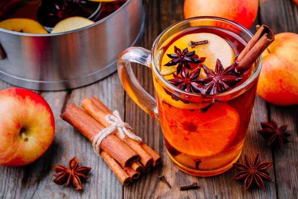 Hot mulled apple cider with with cinnamon sticks