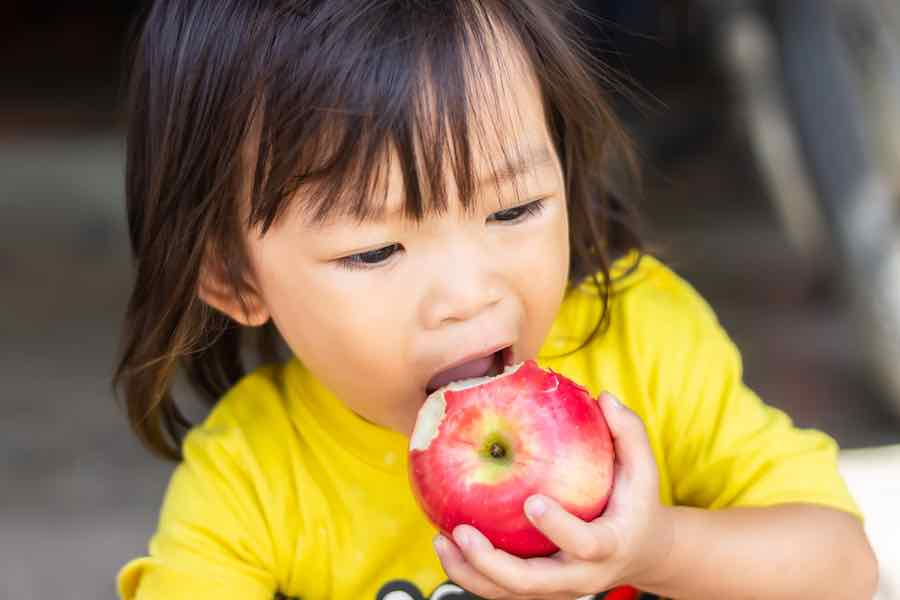 Girl eating red delicious apple