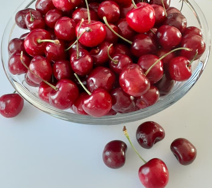 Closeup of bowl of cherries against white surface.  With so many types of cherry trees to choose from, you can have a crop of fresh cherries from your own garden each year.