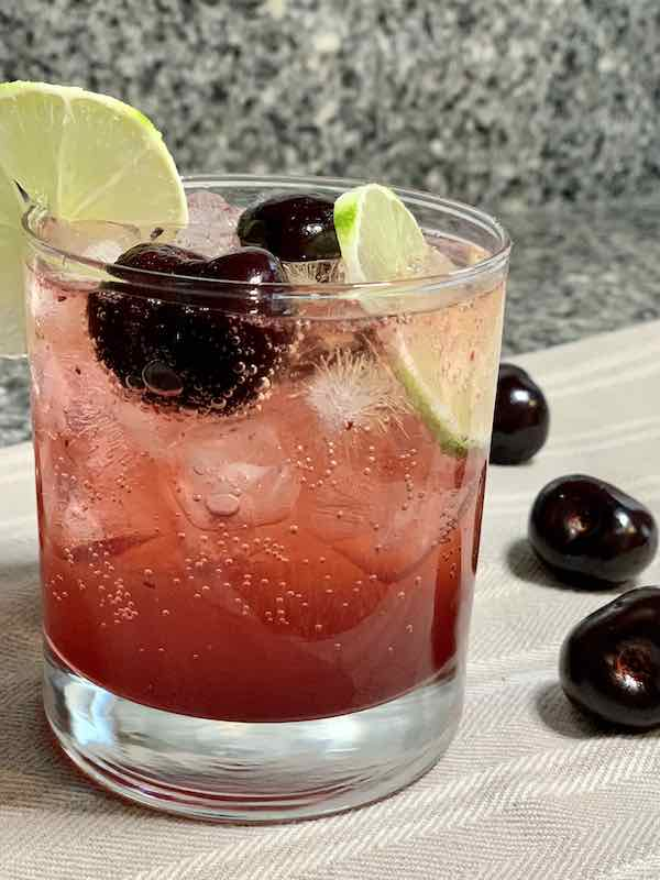 Cherry Limeade In A Glass With Fresh Cherries and Lime Slices