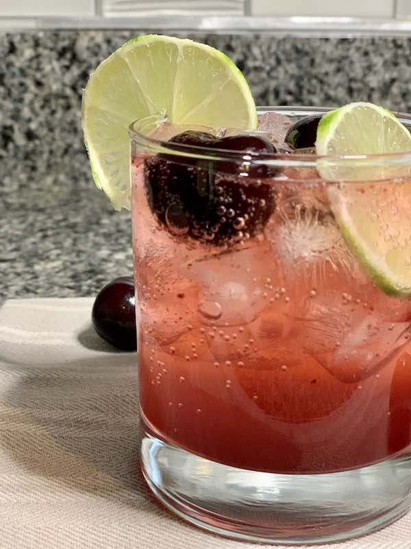 Cherry Limeade In A Glass With Ice And Garnishes