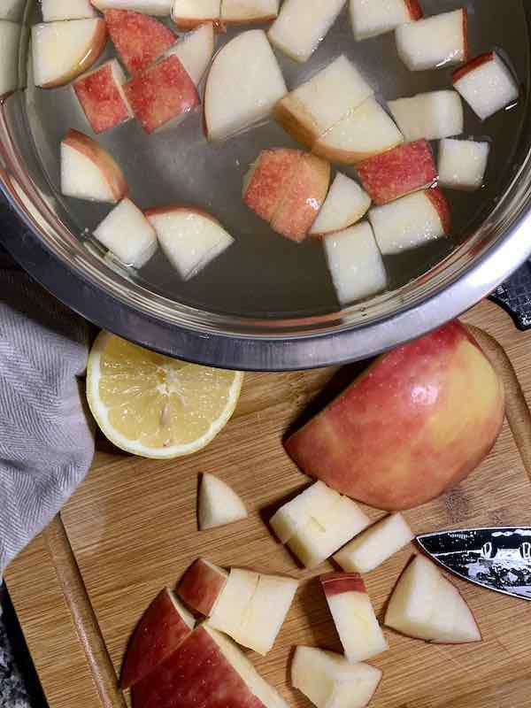 dicing apples and putting them into a bowl of lemon water