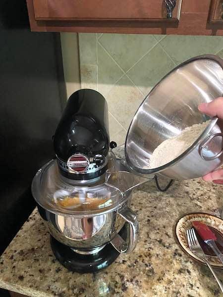 Adding dry ingredients to wet ingredients to make dough.