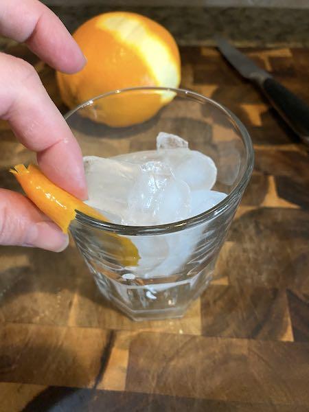 Running a slice of orange rind around the rim of the glass.