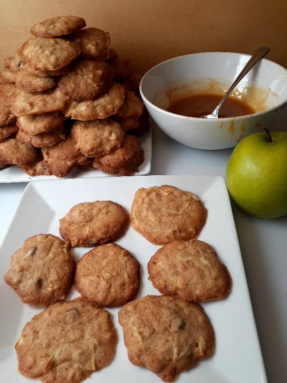 Plain apple cider cookies on a white plate with a larger plate of cookies, a bowl of butterscotch sauce, and a Granny Smith apple in the background.