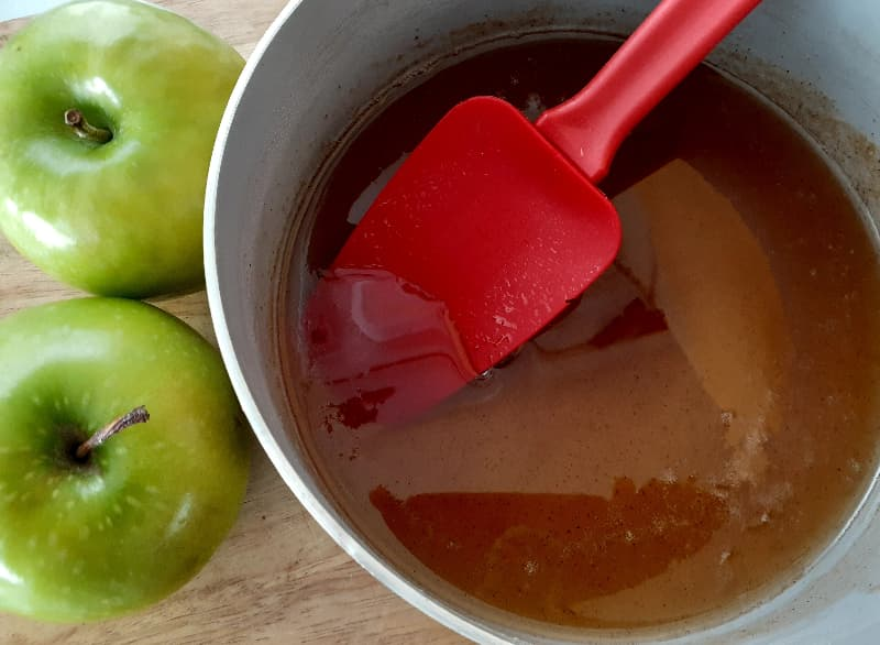 Two Granny Smith apples next to a small pot of honey syrup.