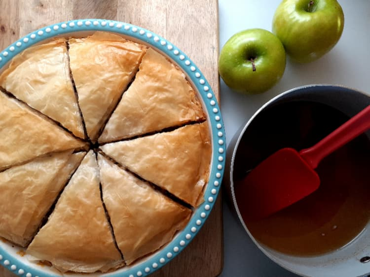 Baked apple pie in a blue and white pie dish with a pot of honey syrup next to it.