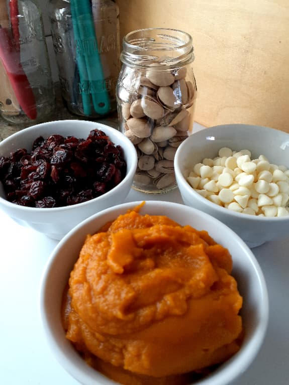 The main flavor elements of the pumpkin muffins -- a bowl of canned pumpkin, a bowl of dried cranberries, a glass jar of pistachios in shells, and a bowl of white chocolate chips.