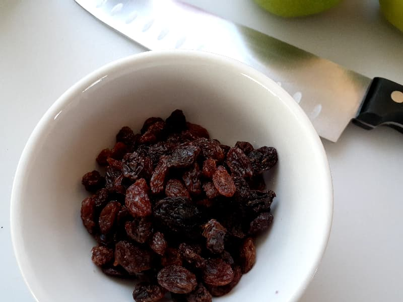 Closeup of small white bowl of raisins with a chef's knife partially in view.