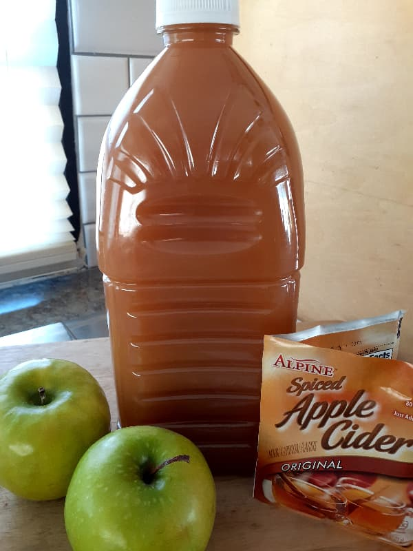 Bottle of apple cider with packets of apple cider mix and two Granny Smith apples in front of it.