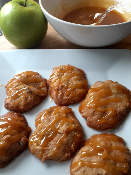 Apple Cider Cookies on a white plate with a white bowl of butterscotch sauce and a Granny Smith apple in the background.