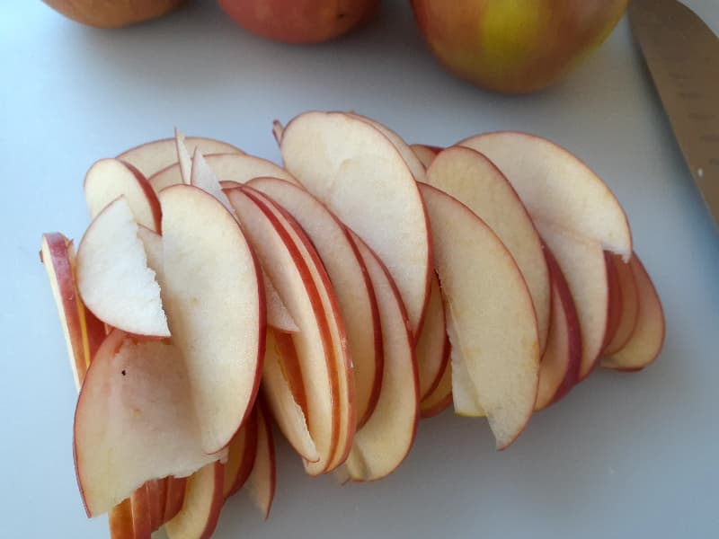 Closeup of a Fuji apple quarter fan cut into slices.