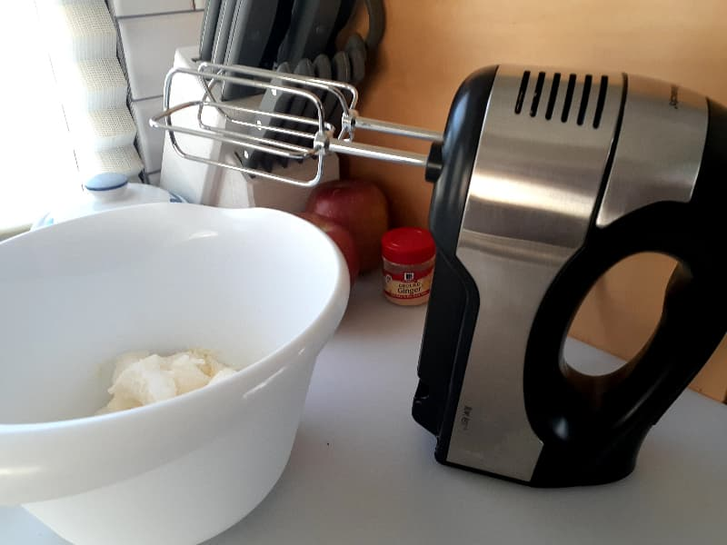An electric hand mixer next to a white mixing bowl.