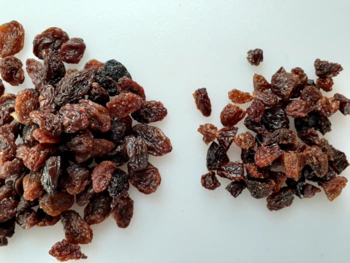 Pile of whole raisins next to small pile of raisins chopped in half or thirds.