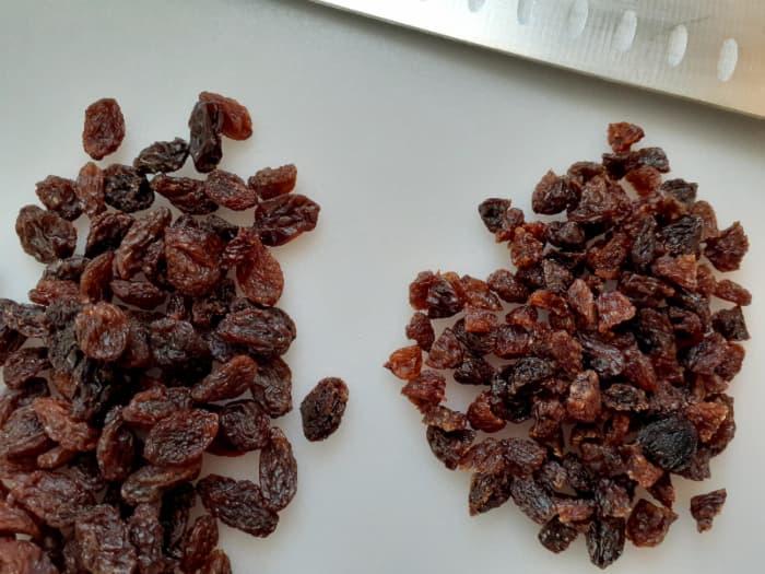 Closeup of pile of chopped raisins next to whole raisins.