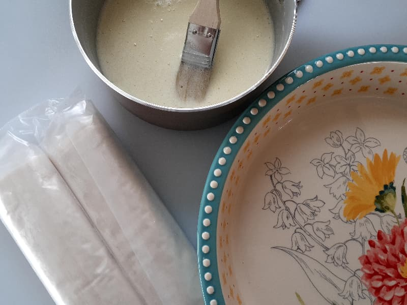 Two sealed rolls of phyllo next to a pie dish and a small pan of melted butter with a pastry brush in the butter.