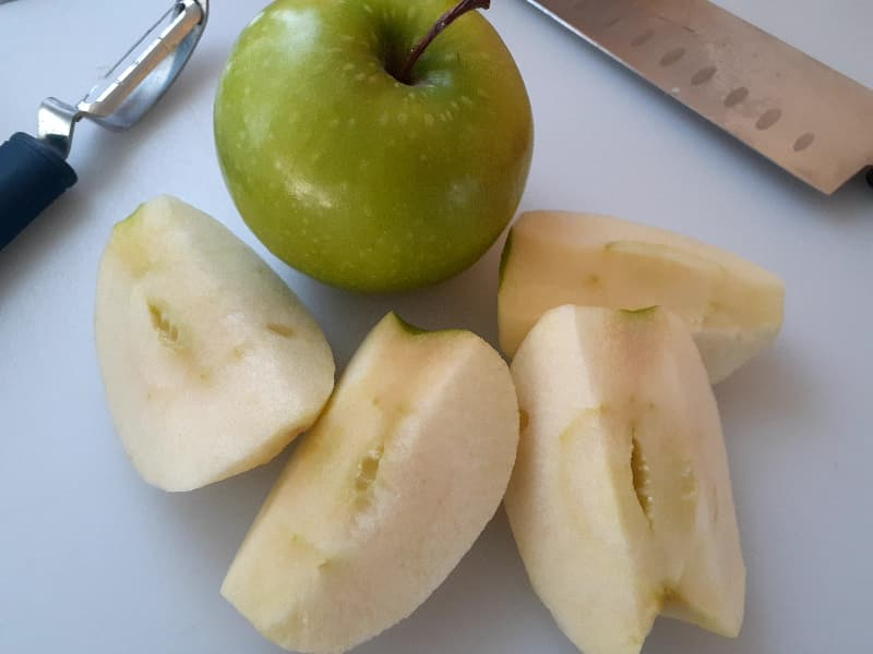 Whole Granny Smith apple next to a Granny Smith apple that has been peeled, quartered, and the cores cut off with a peeler and chef's knife partially in view.