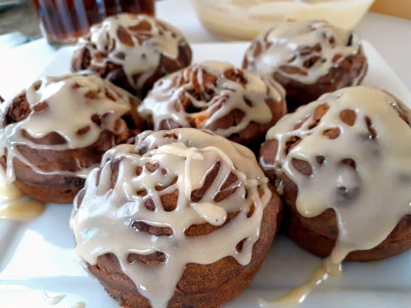 Glazed pumpkin muffins on a white plate.