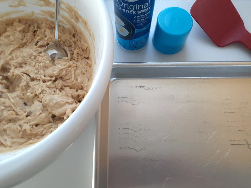 A white bowl of apple cider cookie dough next to a baking sheet with a can of cooking spray and a red spatula partially in view