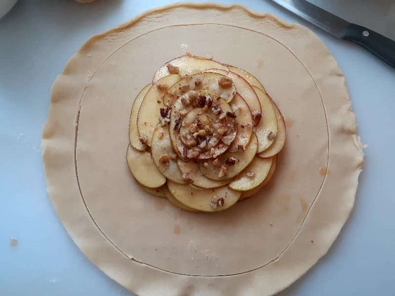 Pie crust that has been trimmed to a circle about 1 1/2 - 2 inches larger than the circle of apples in the middle of the pie crust.