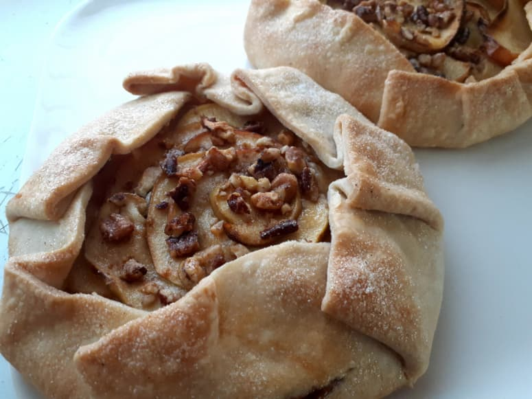 Two baked Apple Cheesecake Galettes on a white plate.