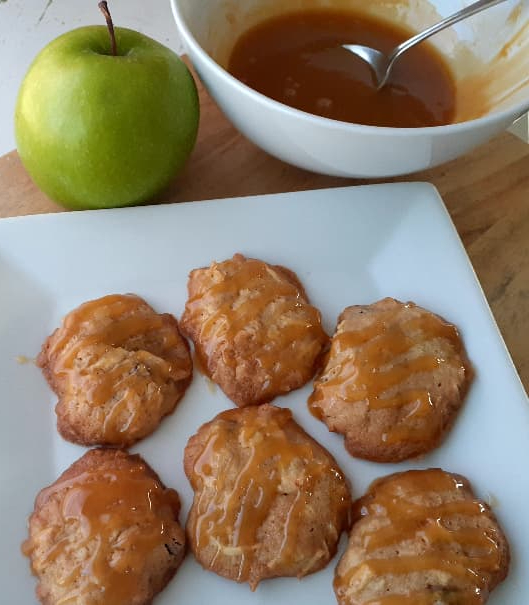 Apple cider cookies on a white plate with butterscotch drizzle on them -- a white bowl of butterscotch sauce and a Granny Smith apple are in the background.