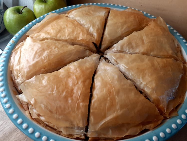 Golden brown baked apple pie with Granny Smith apples in the background.