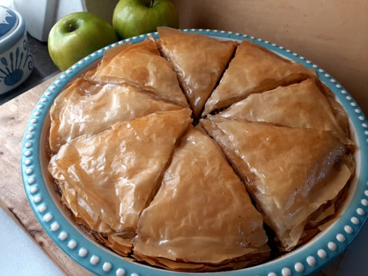 Baked apple pie with syrup poured over it.