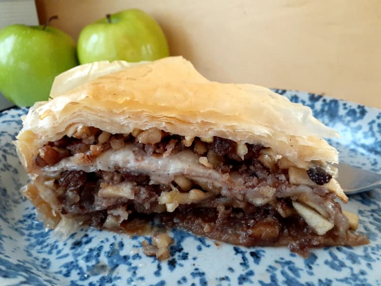 Wedge of apple pie on a blue and white plate with Granny Smith apples in the background.