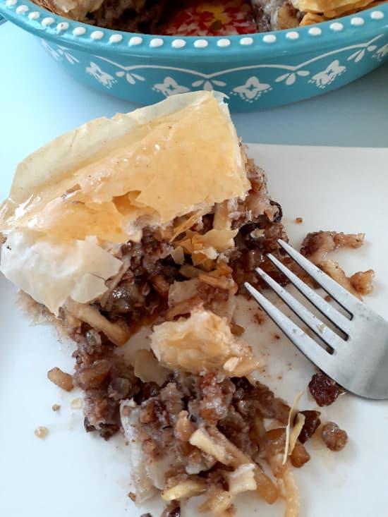 Closeup of half-eaten apple pie wedge with fork and pie dish partially showing.