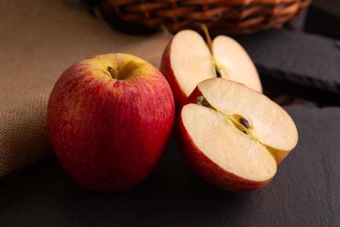 A whole red apple next to a red apple cut in half against a dark background -- the apples are similar to Pacific Rose Apple tree apples.
