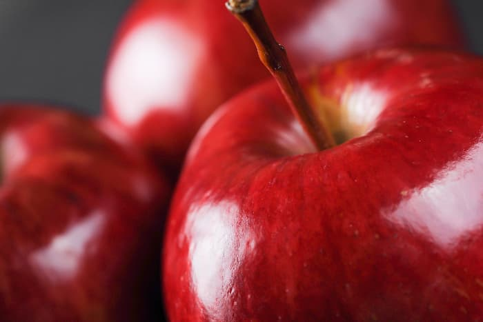 Closeup of bright, red apples that closely resemble the fruit from the rare Rave Apple tree.