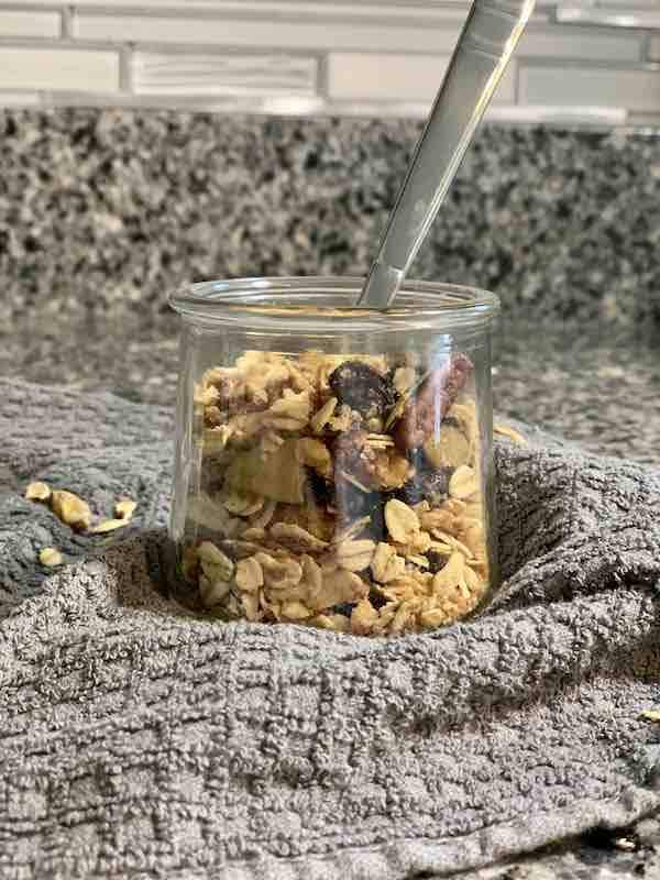 Closeup of apple granola in a glass jar with a spoon it -- a great recipe idea for Kanzi apples
