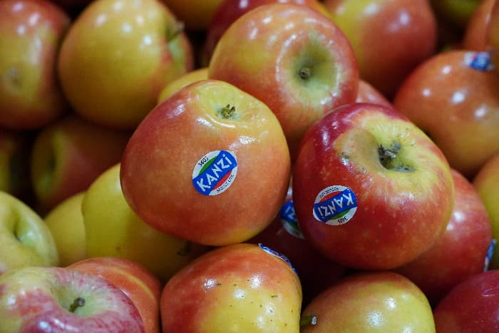 """Closeup of apples with labels reading """"Kanzi"""" on them."""