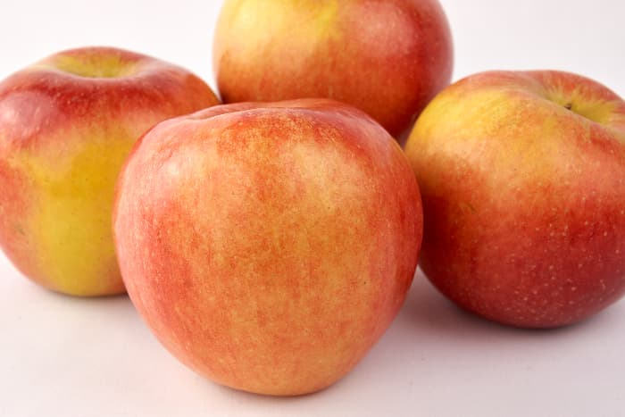 Group of Koru apples on white background.