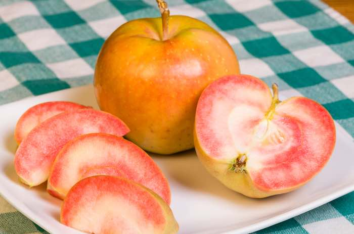 Pink Pearl Apples freshly sliced onto a white plate.