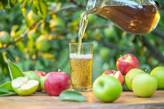 A closeup of apple juice being poured from a glass pitcher into a glass on a wooden table with red and green apples on it.