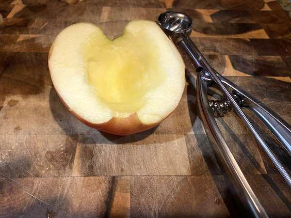 Apple half prepared with melon ball scooper.