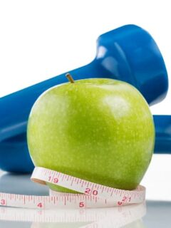 A Pristine Apple with a blue dumbbell, a plastic tape measure, and a glass of water.