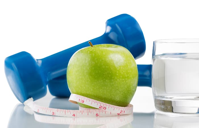 Closeup of a green apple from the Pristine Apple tree, a blue dumbbell, a plastic measuring tape, and a small glass of water.