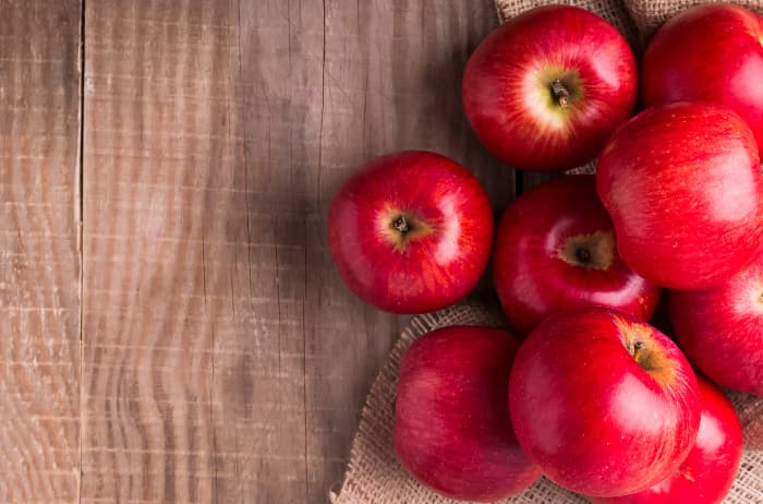 Shiny red apples on a wooden table that closely resemble the fruit of a SnowSweet Apple tree