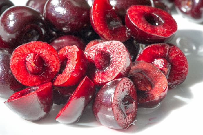 Sweet red cherries, like the Bing cherry and the Tulare cherry, cut in half with pits.
