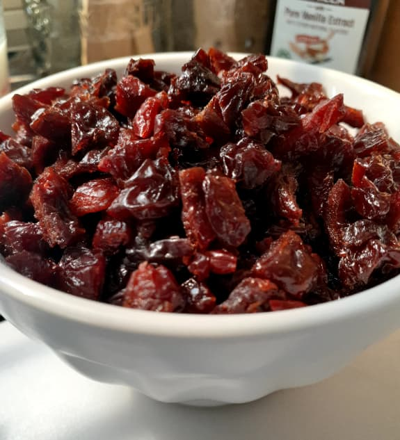Closeup of a white bowl of dried cherries.