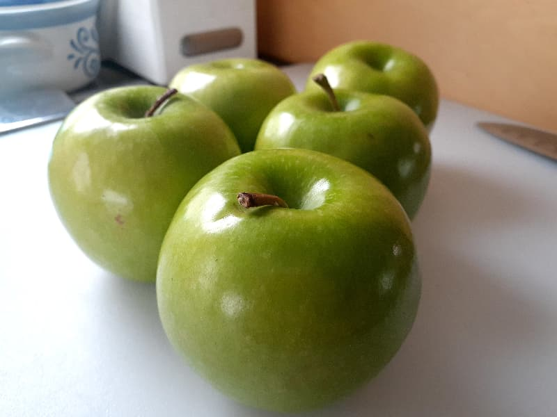 Closeup of Granny Smith apples on a white surface.