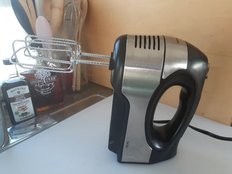 An electric handmixer with jars of wooden spoons, a bottle of vanilla, and a bottle of maple syrup in the background.