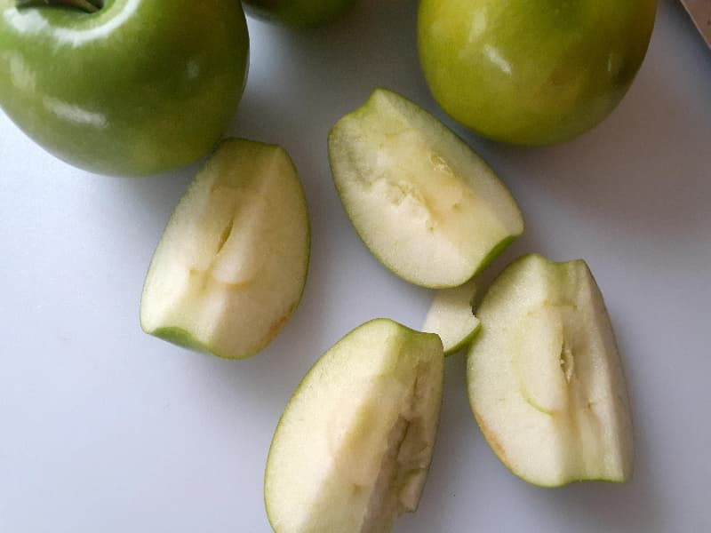 Closeup of 4 Granny Smith apple quarters next to a couple whole Granny Smith apples.
