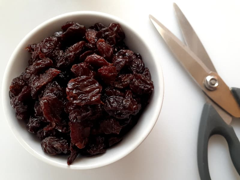 A closeup of a small white bowl of dried cherries and kitchen shears partially in view.