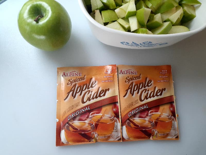 Two packets of Alpine apple cider mix on a white surface next to a whole Granny Smith apple and a small baking dish of cut Granny Smith apples.