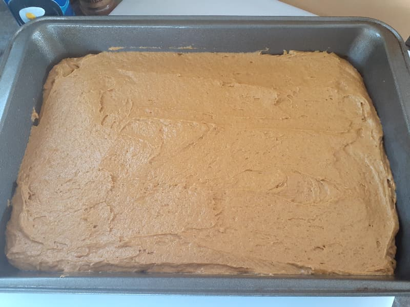A close up of the batter for pumpkin bars spread into a 9 x 13 baking pan.