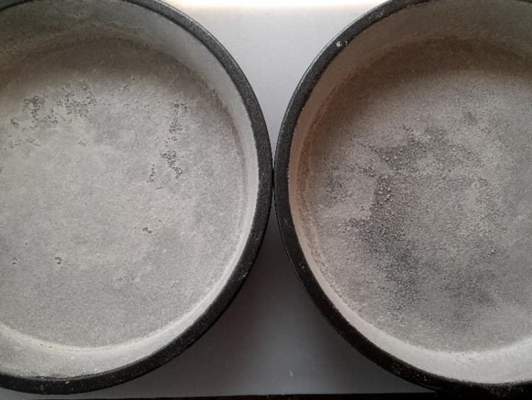 Two 9-inch round cake pans greased and floured for baking.